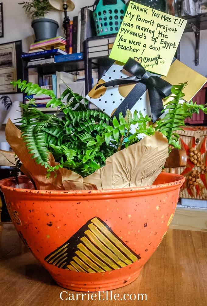 Planting pot with painted gold and black pyramid filled with a live fern