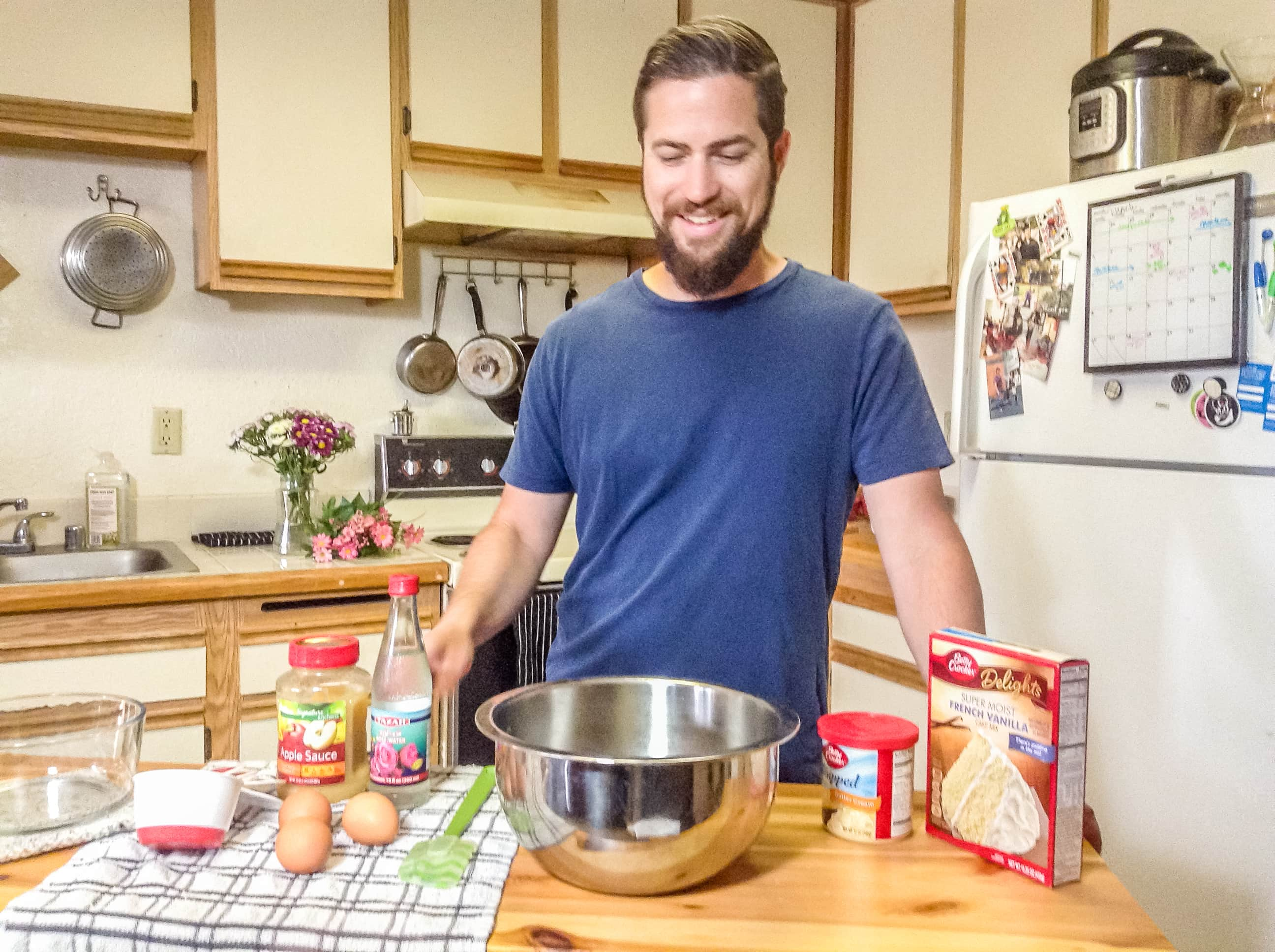 Man standing at kitchen table with ingredients for cake in front of him