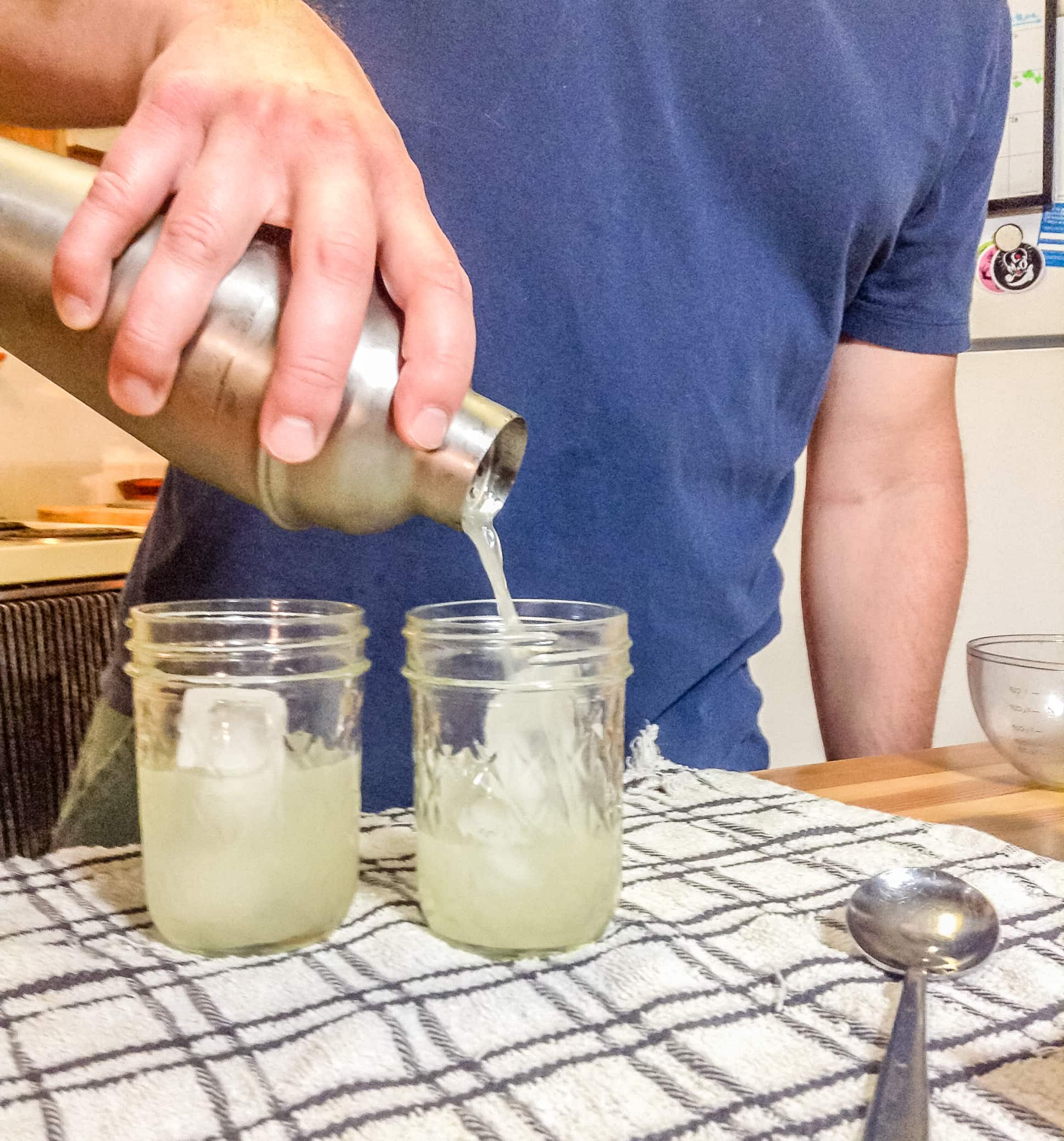 photo of man pouring cocktail from a shaker over ice in a glass