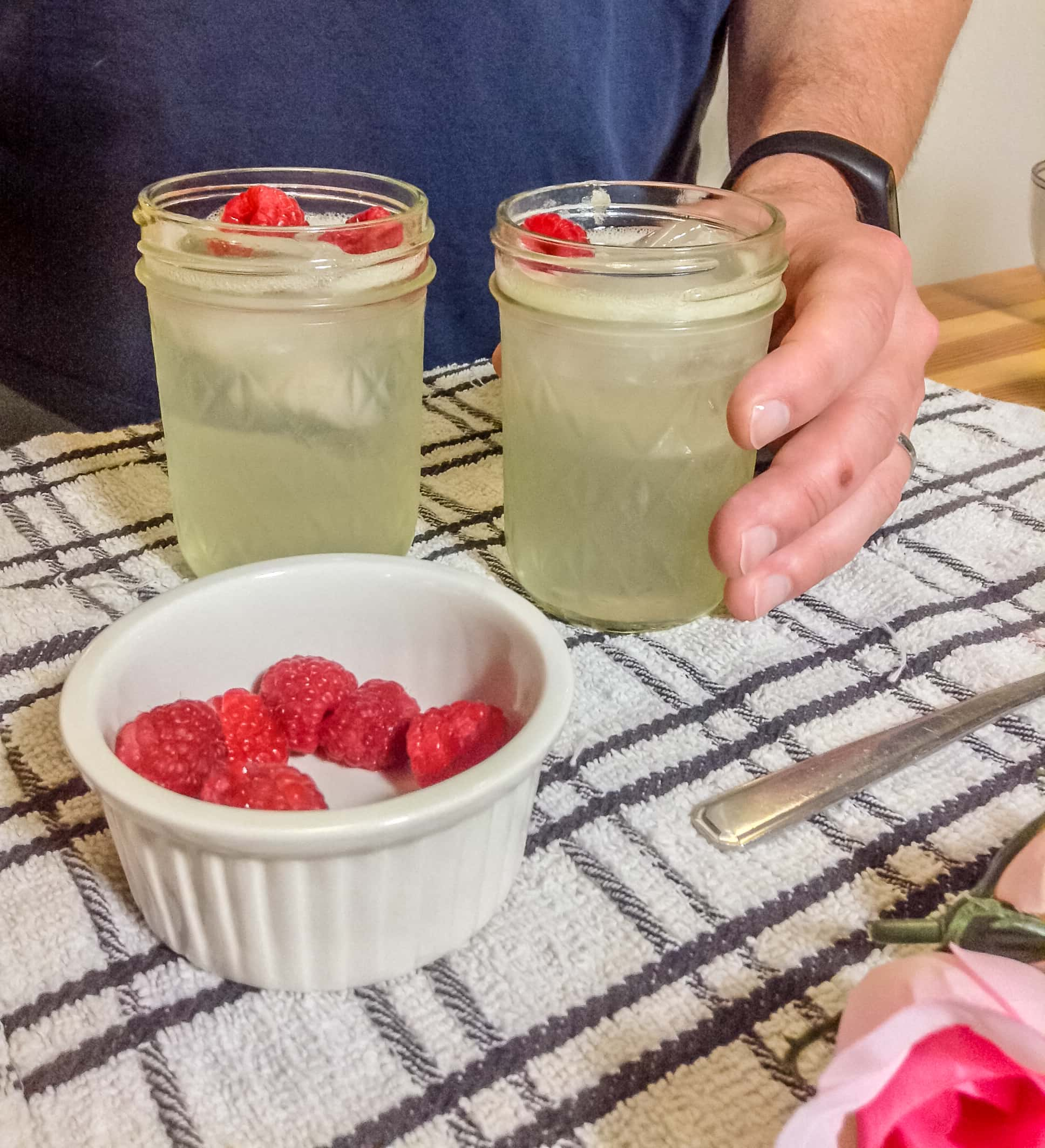 Photo of rose cocktail with raspberries on top and a bowl
