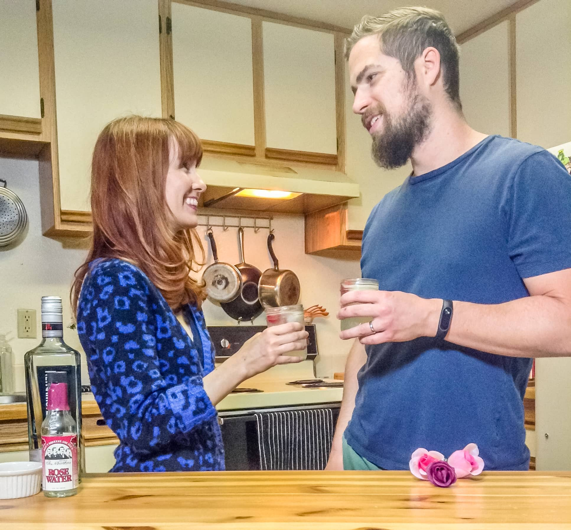 Couple toasting cocktails in the kitchen