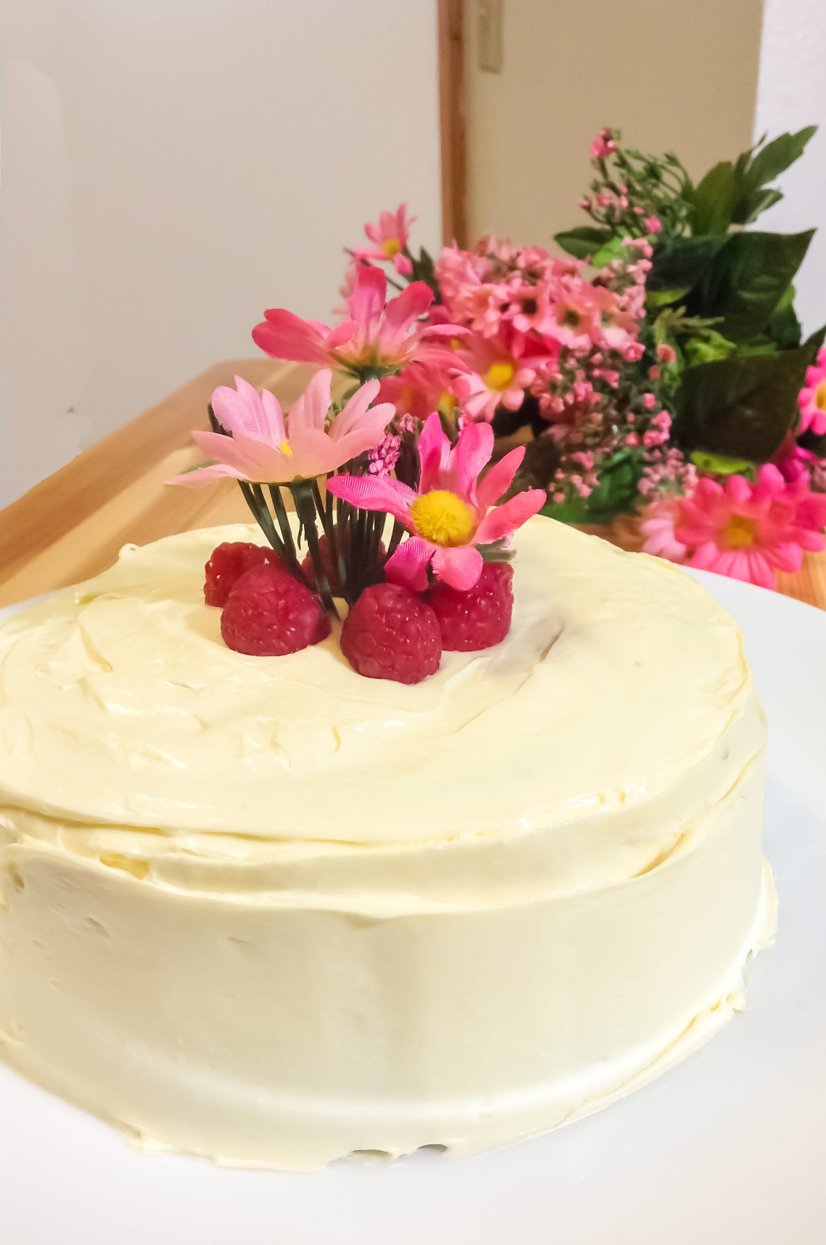 White cake topped with pink flowers and raspberries